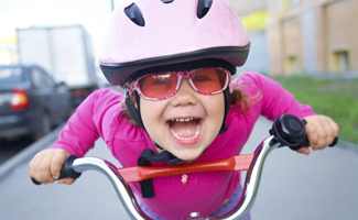 Kid riding a bike with helmet and sunglasses