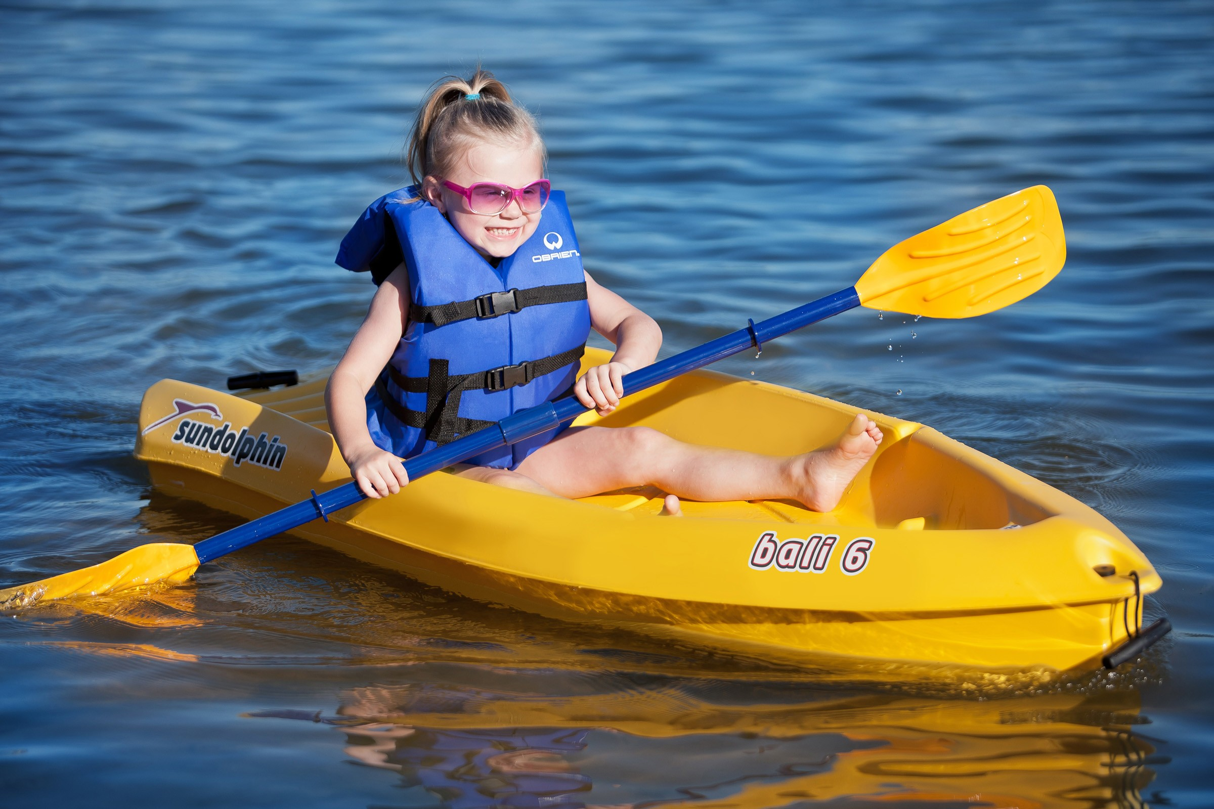 Kid paddling in a boat with sunglasses on