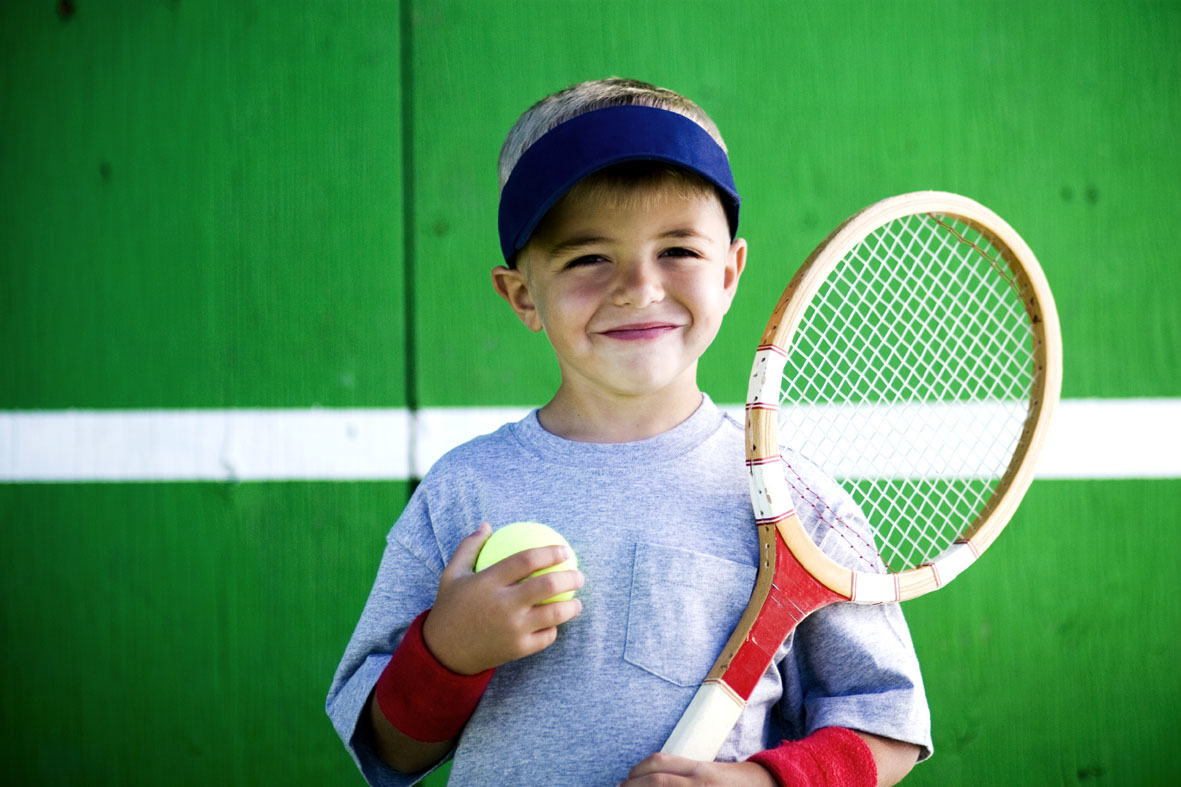 Kid holding a tennis ball and tennis racket