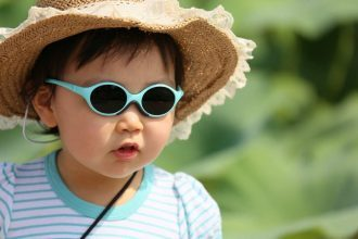 Child wearing hat and sunglasses for UV protection.