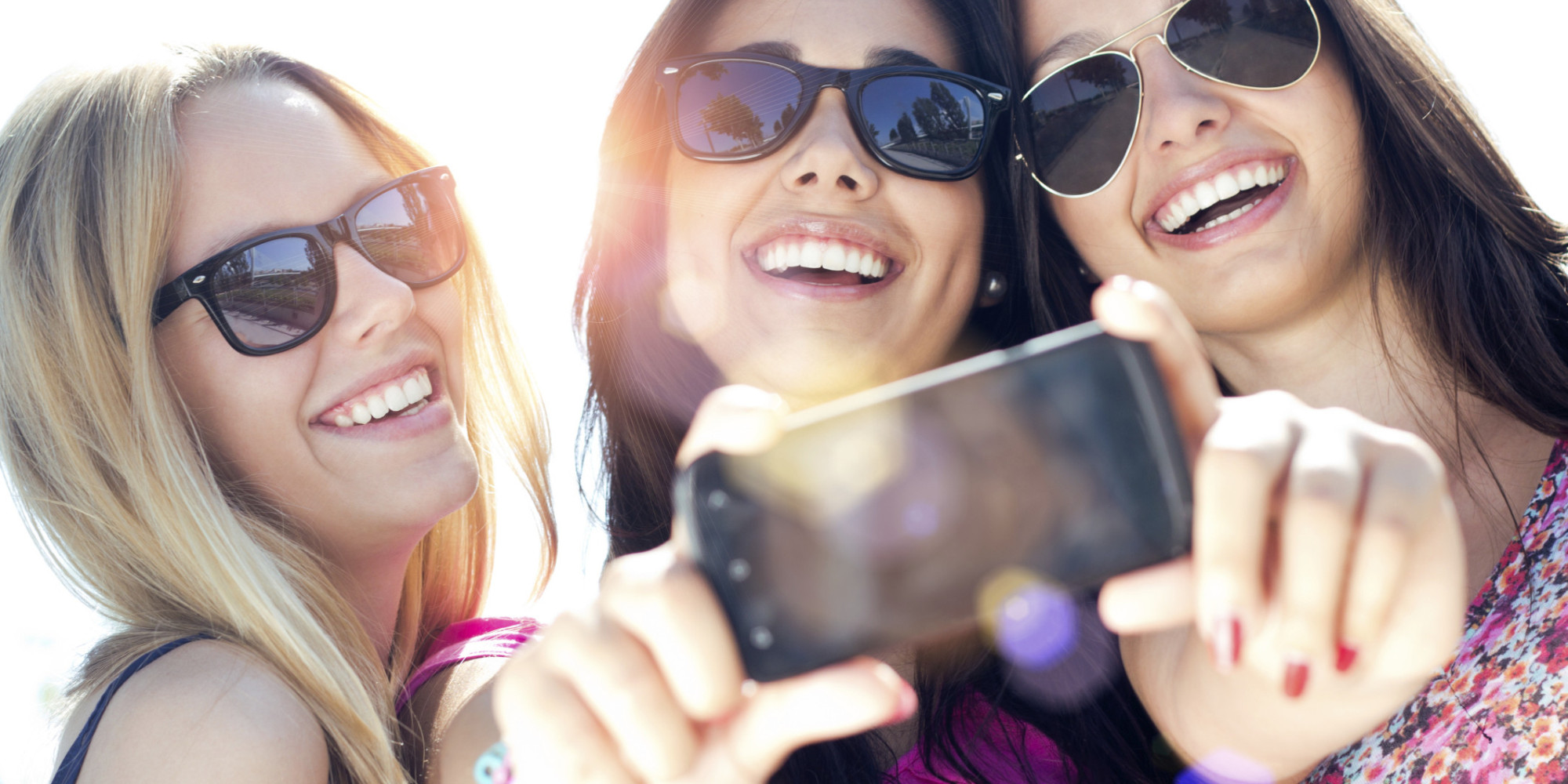 Three teenagers taking a selfie while wearing sunglasses.